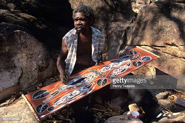 Aboriginal artist Simon Badari painting a bark in his clan country near Injalak hill western Arnhem Land Painting of his totems Kumoken the...
