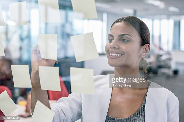 Aboriginal Australian businesswoman smiling, using sticky notes