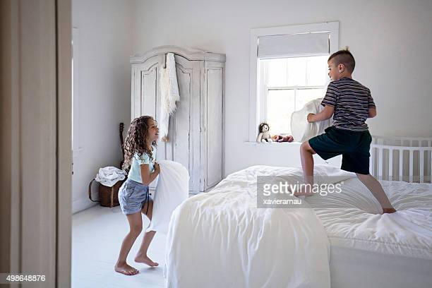 Aboriginal Australian siblings fighting with pillows