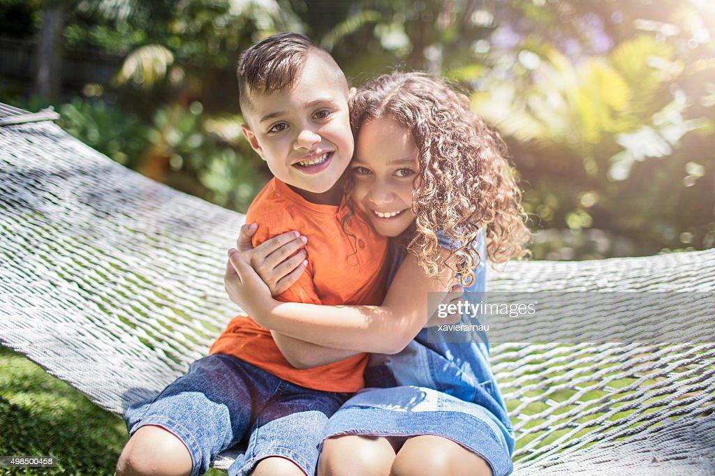 Aboriginal australian siblings hugging in the garden : Stock Photo