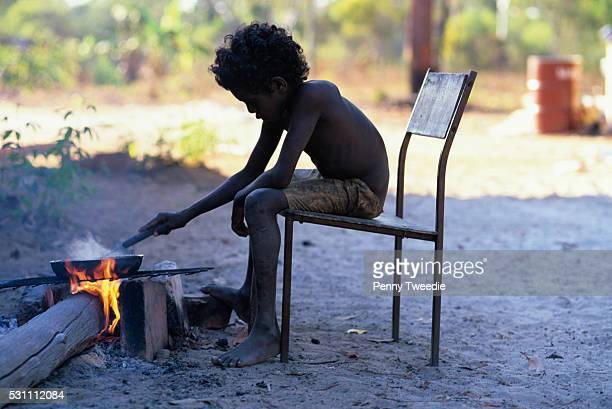 Aboriginal boy cooking over a camp fire in Central Arnhem Land