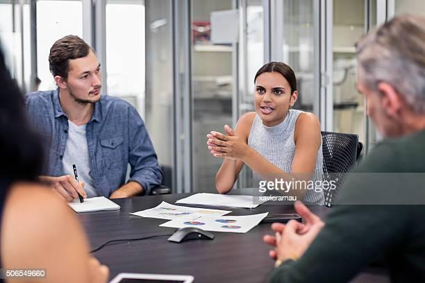 Aboriginal mujer de negocios hablando en una reunión
