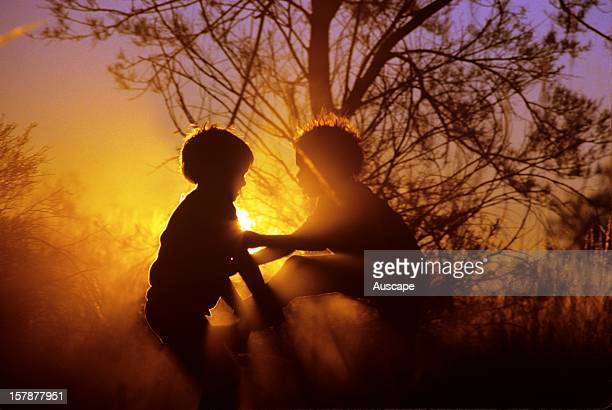 Aboriginal children in silhouette at sunset on the Canning Stock Route Little Sandy Desert Western Australia