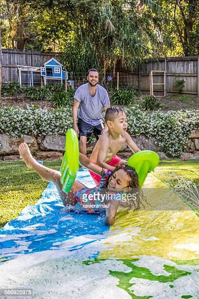 Aboriginal children on slip 'n slide in the garden