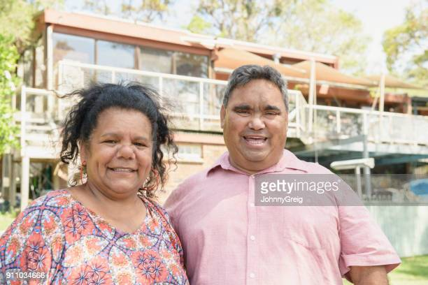 Aboriginal couple smiling toward camera outside house