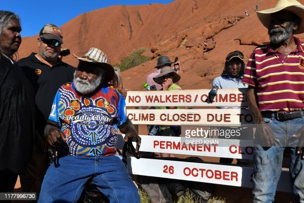 Aboriginal elders stand beside new signage at the base of Uluru, also known as Ayers Rock, ahead of the day's end marking the start of a permanent...