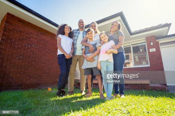 Aboriginal Family standing in front of their home.