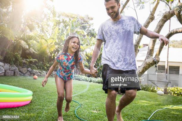 Aboriginal father and daughter having fun at backyard garden