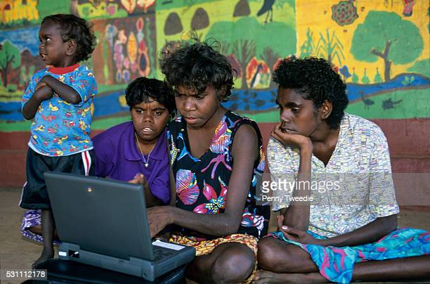 Aboriginal girls using a computer outside the community centre at Ramingining Arnhem Land