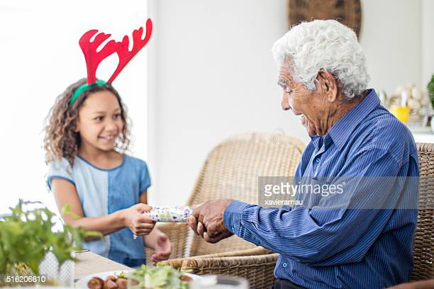 Aboriginal grandfather and granddaughter pulling Christmas cracker at table