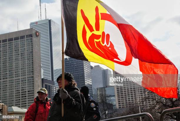 Aboriginal Indian man from the Chippewa First Nation carries a large flag during a rally in Toronto Ontario Canada on February 042017