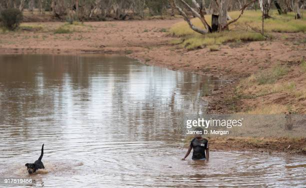 Aboriginal Kids swimming with dogs in the Todd river in January 12th 2018 in Alice springs Australia