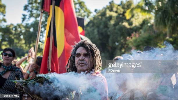 Aboriginal  man conducts a 'smoking ceremony' to lead parade.