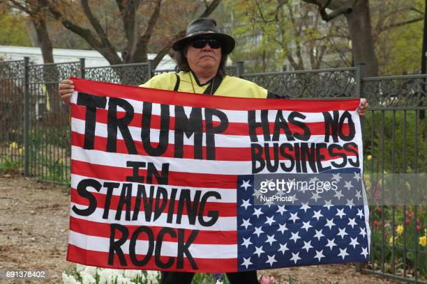 Aboriginal man holds an upsidedown American flag with the words 'Trump has no business in Standing Rock' as hundreds of Canadians took part in a...