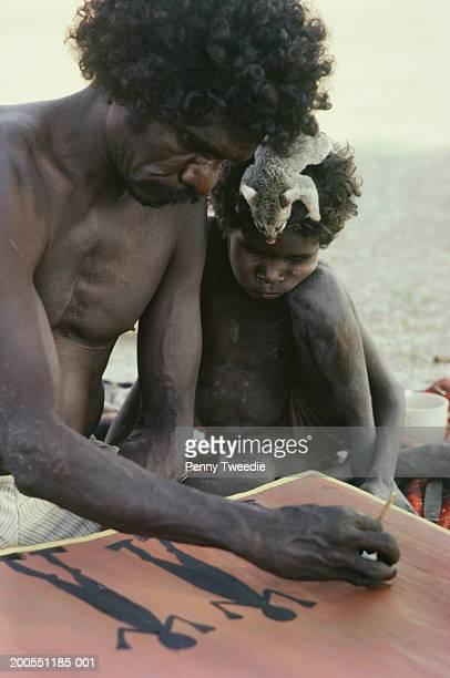 Aboriginal man painting, boy (4-5) watching, Arnhemland, Australia