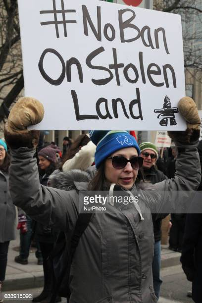 Aboriginal member of the First Nations holds a sign saying 'No Ban on Stolen Land' as thousands of Canadians took part in a massive protest against...