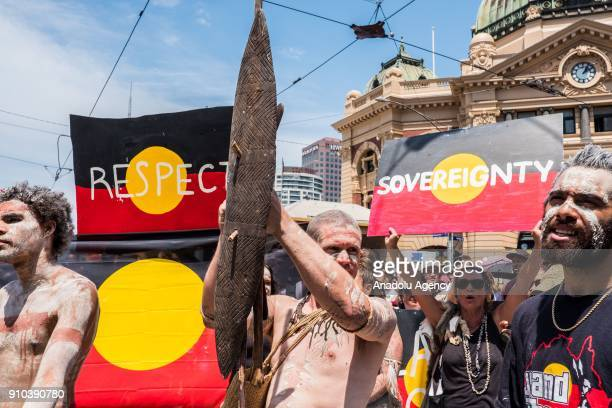 Aboriginal men dressed in traditional Aboriginal attire standing in front of placards reading 'respect' and 'sovereignty' during a protest by...