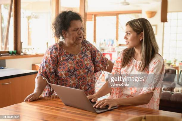 Aboriginal mother talking to daughter working at home on laptop
