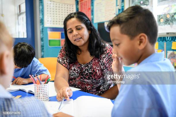 aboriginal primary school teacher helping young boy in the classroom - australia stock pictures, royalty-free photos & images