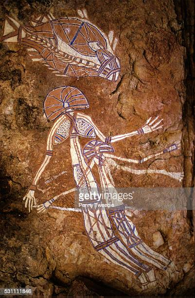 Aboriginal rock art at Nanguluwarr one male one female and barramundi fish in Xray style Arnhem Land