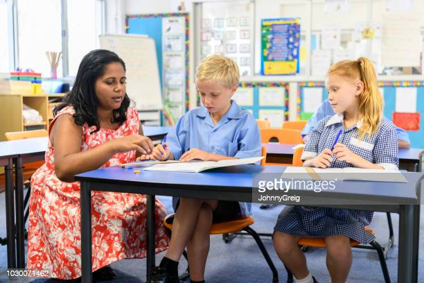 aboriginal school teacher explaining to boy and girl sitting in classroom - uniform stock pictures, royalty-free photos & images