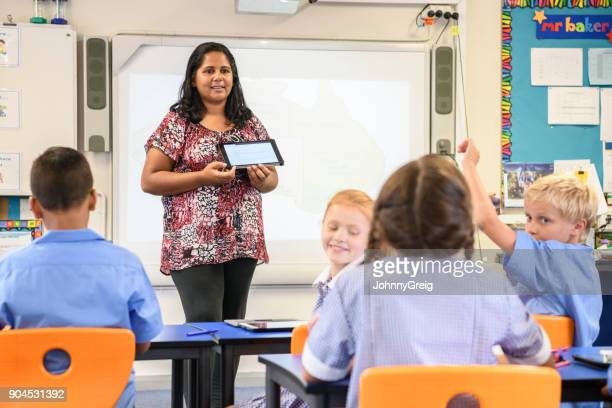 Aboriginal teacher holding tablet and watching children in the classroom
