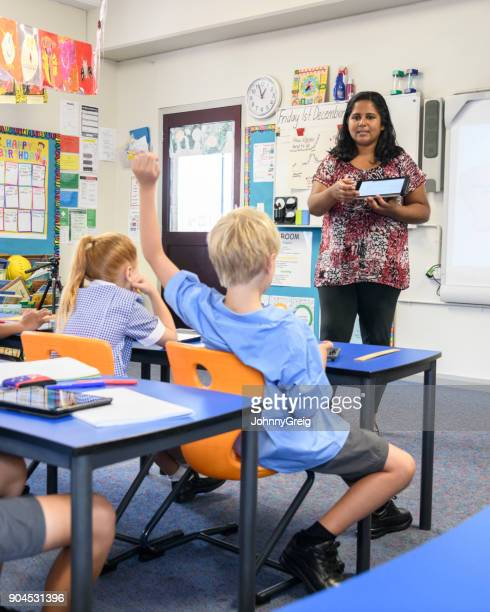 Aboriginal teacher in classroom with digital tablet and young boy with arm raised