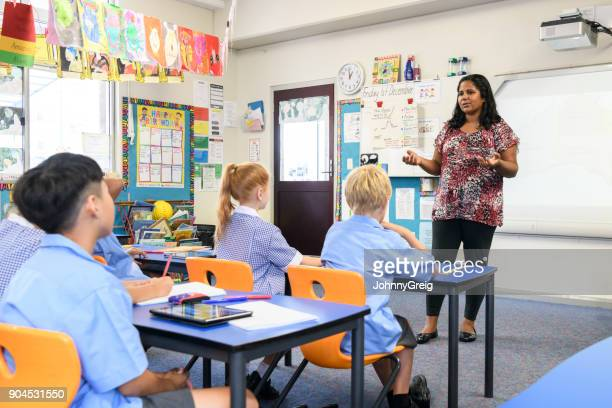 Aboriginal teacher standing at front of classroom and explaining to children