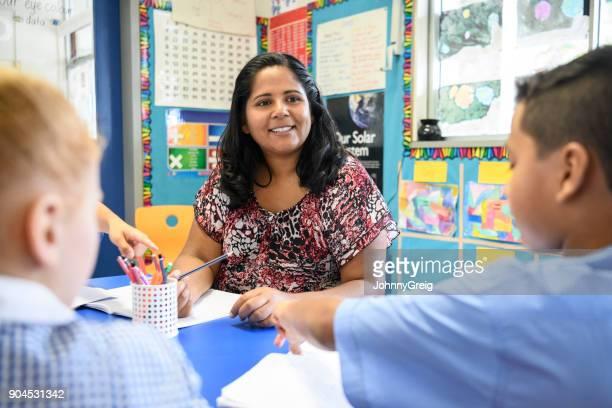 Aboriginal teacher working in primary school and looking at school children