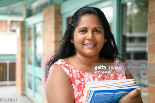 Aboriginal woman holding text books outside school