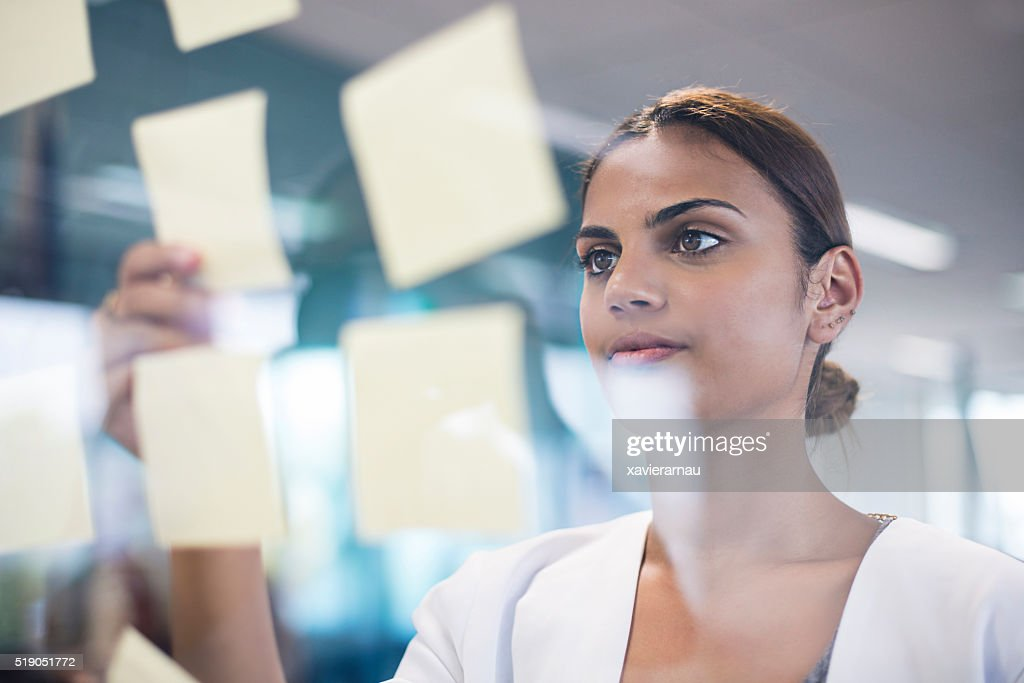 Aboriginal woman picking up an idea note fro the board : Stock Photo
