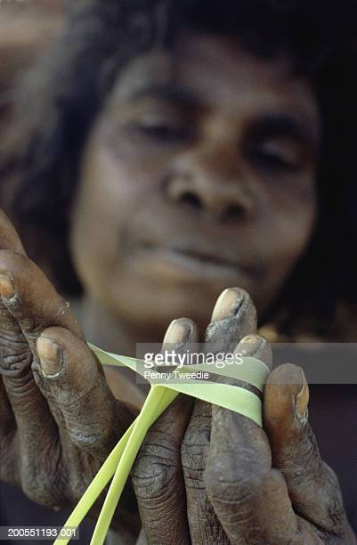 Aboriginal woman splitting pandanus for weaving, close-up, Arnhemland, Australia