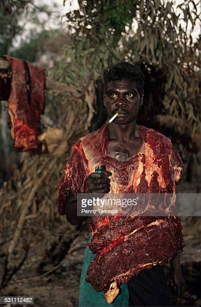Aboriginal young men return from hunting with buffalo which they take off the bone and then carry the meat by wearing it Central Arnhem Land Buffalo...