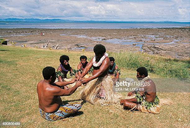 Aborigines preparing a traditional drink made from kava roots and coconut milk Fiji