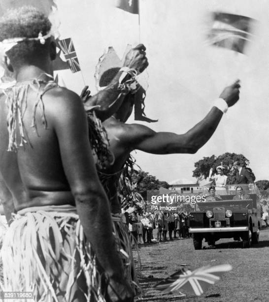 Aborigines wave flags for the Queen and Duke of Edinburgh as they drive round Townsville Queensland during their tour of Australia