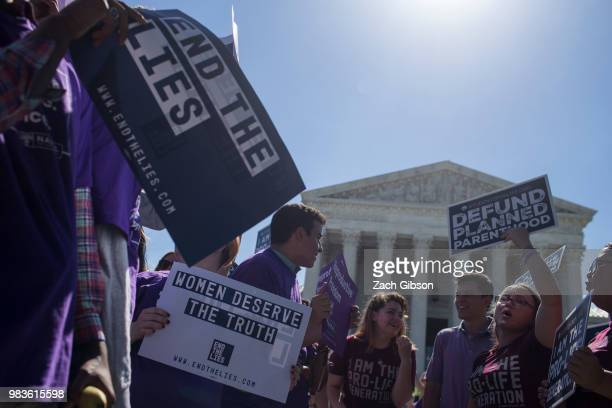 Abortion opponents and supporters hold sings in front of the US Supreme Court on June 25 2018 in Washington DC The high court is expected to issue...