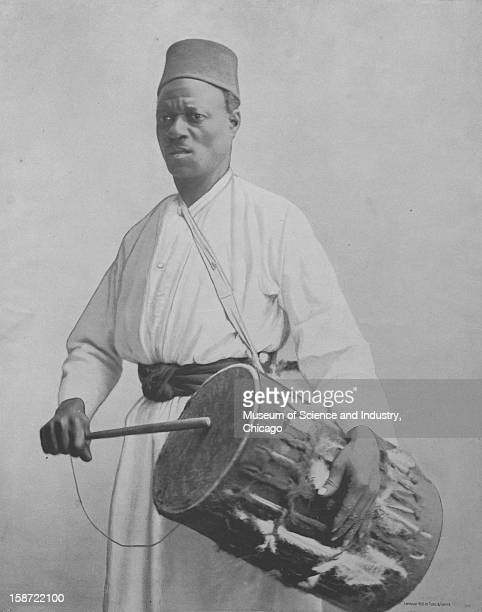 Abou Bakr Ghindi a drum beater from the Upper Soudan wearing traditional garb as seen at the World's Columbian Exposition in Chicago Illinois 1893...