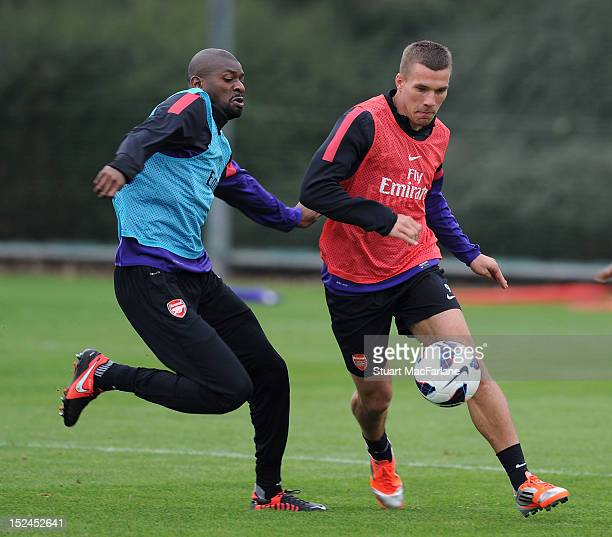Abou Diaby and Lukas Podolski of Arsenal during a training session at London Colney on September 21, 2012 in St Albans, England.