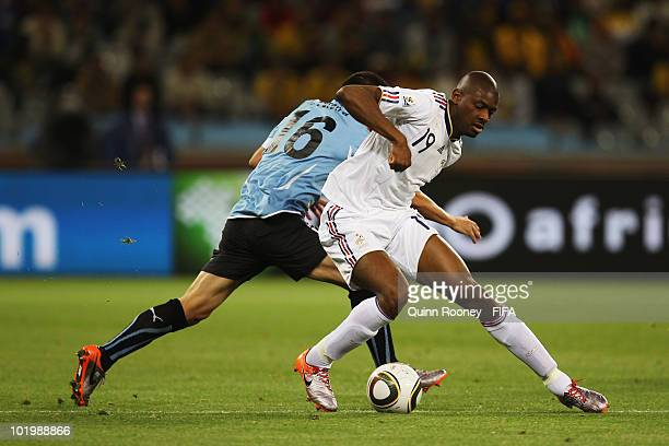Abou Diaby of France and Maximiliano Pereira of Uruguay battle for the ball during the 2010 FIFA World Cup South Africa Group A match between Uruguay...