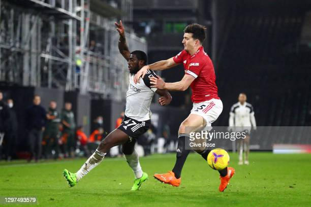 Aboubakar Kamara of Fulham and Harry Maguire of Manchester United battle for possession during the Premier League match between Fulham and Manchester...