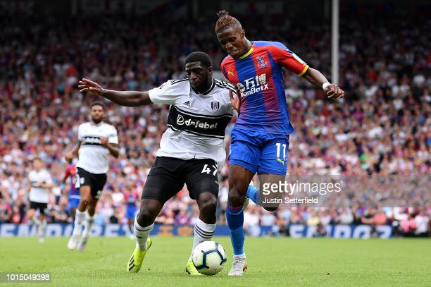 Aboubakar Kamara of Fulham battles for possession with Wilfried Zaha of Crystal Palace during the Premier League match between Fulham FC and Crystal...