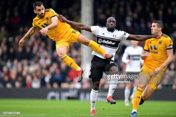 Aboubakar Kamara of Fulham is challenged by Jonny Otto of Wolverhampton Wanderers and Conor Coady of Wolverhampton Wanderers during the Premier...