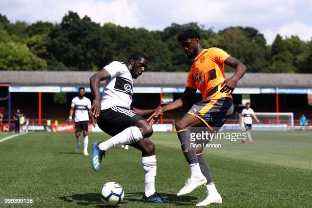 Aboubakar Kamara of Fulham is challenged by Tyler Blackett of Reading during the preseason friendly between Reading and Fulham at the EBB Stadium on...