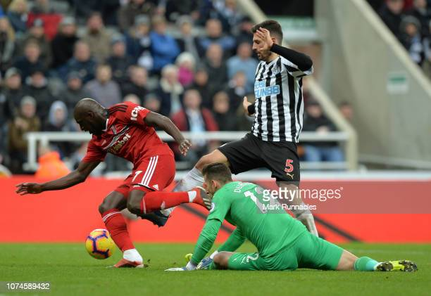 Aboubakar Kamara of Fulham is tackled by Fabian Schar and Martin Dubravka of Newcastle during the Premier League match between Newcastle United and...