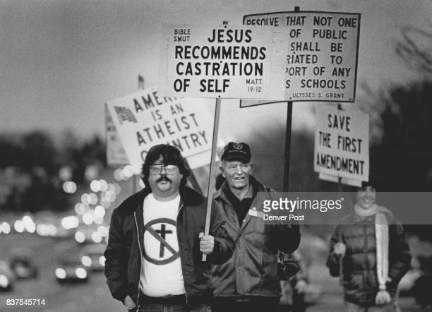 About 15 atheists walked with signs outside First Nazarene Church Sunday evening before services that included preacher Jerry Falwell Tom Holbo...