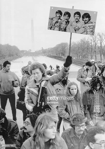 About 1500 fans of John Lennon gathered on the steps of the Lincoln Memorial 12/10 to mourn his death A fan holds a poster of the Beatles with the...