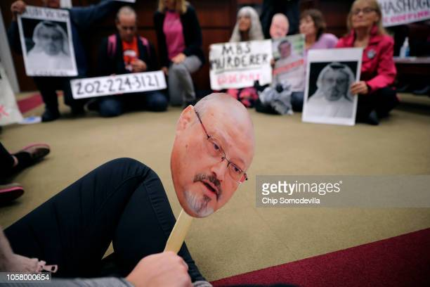 About 17 protesters from Code Pink Women for Peace hold paper masks of Saudi dissident and Washington Post columnist Jamal Khashoggi while...