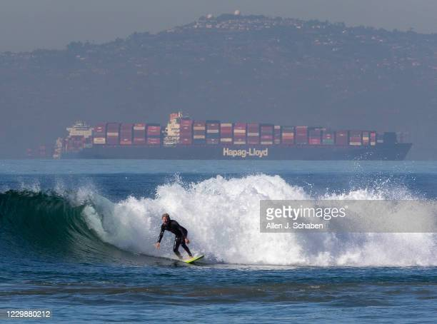 About 20 container ships wait in line to be unloaded at the Ports of LA and Long Beach as a surfers rides a wave in Huntington Beach Monday, Nov. 30,...