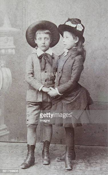 About 6yearold boy and 7yearold girl holding their hands Both with hat Full figure About 1885 Photograph by Carlo Zamboni / Fiume Photograph