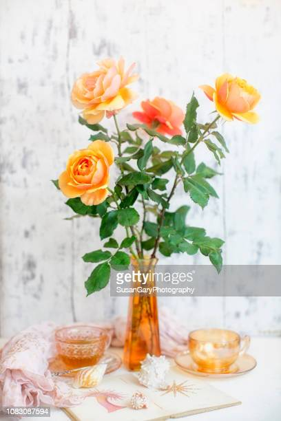 about face orange colored roses in amber glass vintage vase - yellow roses stock photos and pictures